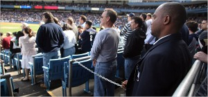 Photo of Yankee Stadium security guards chaining in fans for God Bless America